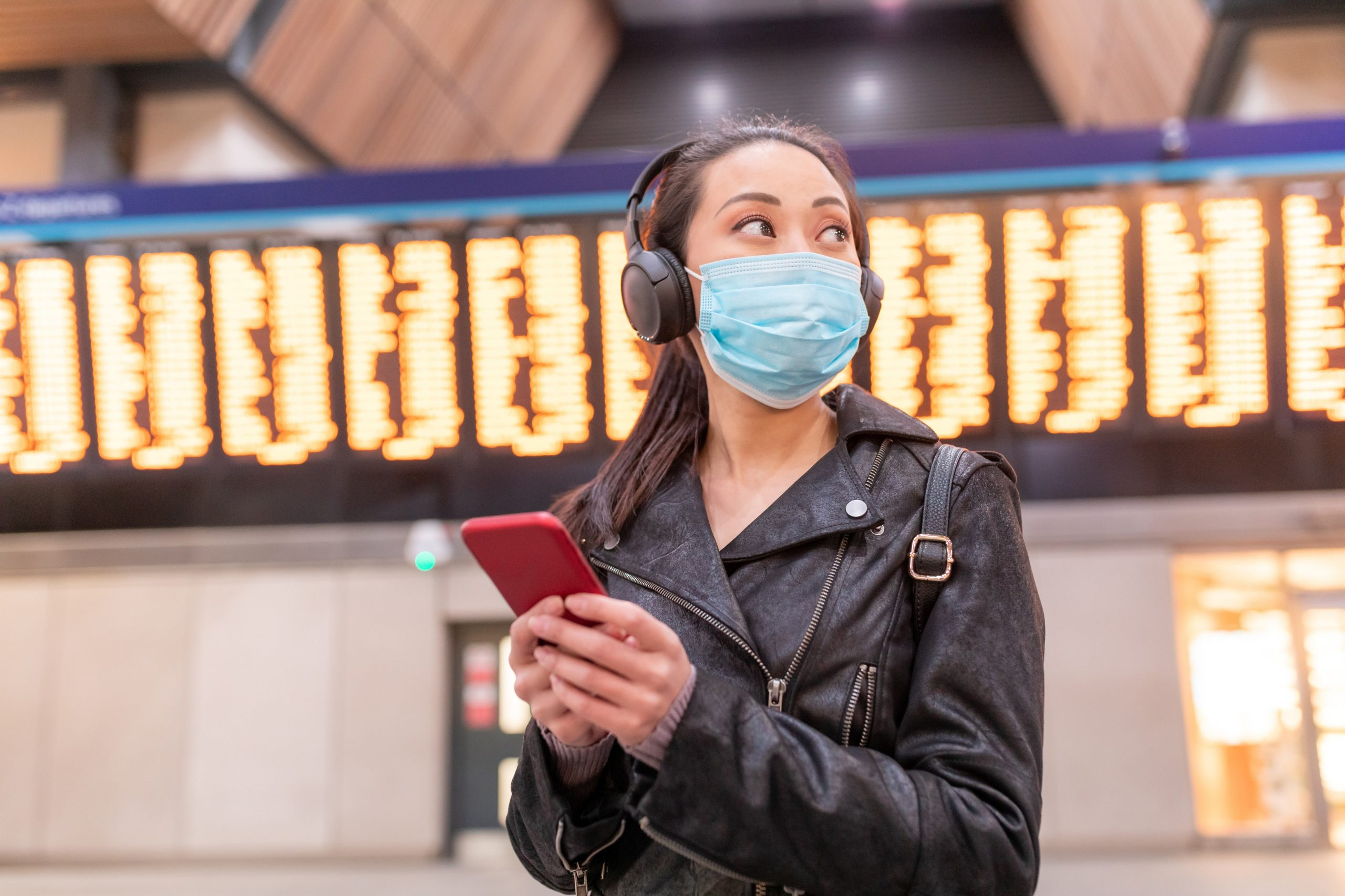 Chinese woman wearing face mask at train station and maintaining social distance - young asian woman using smartphone and looking away with departure arrivals board behind