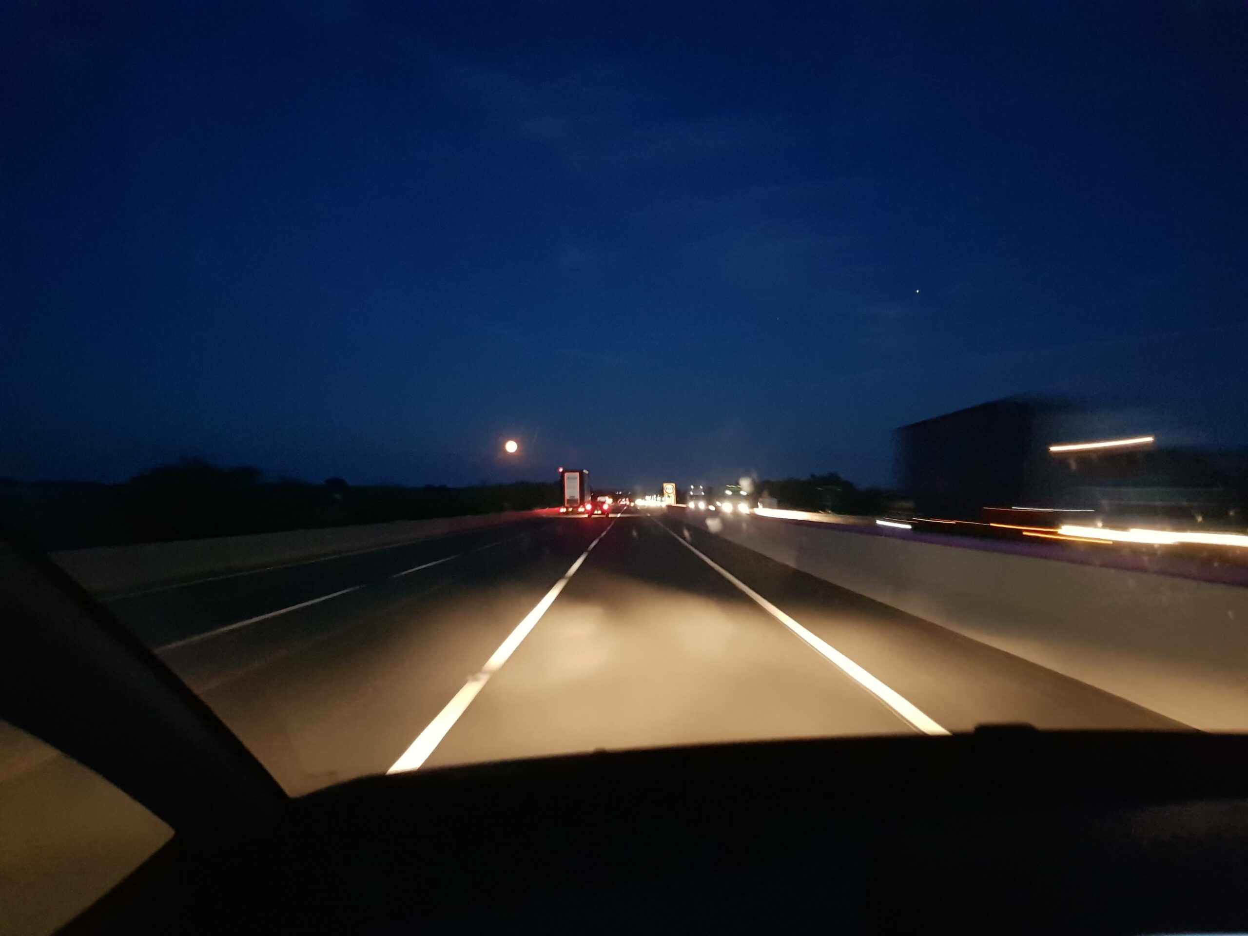 View from the passenger seat of a car along a moonlit motorway