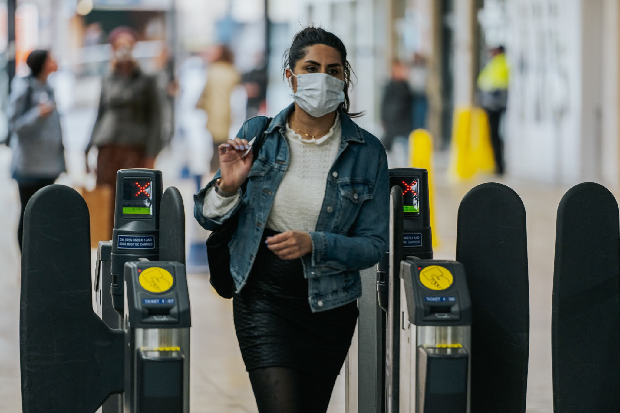Woman in facemask exiting train station through ticket gate